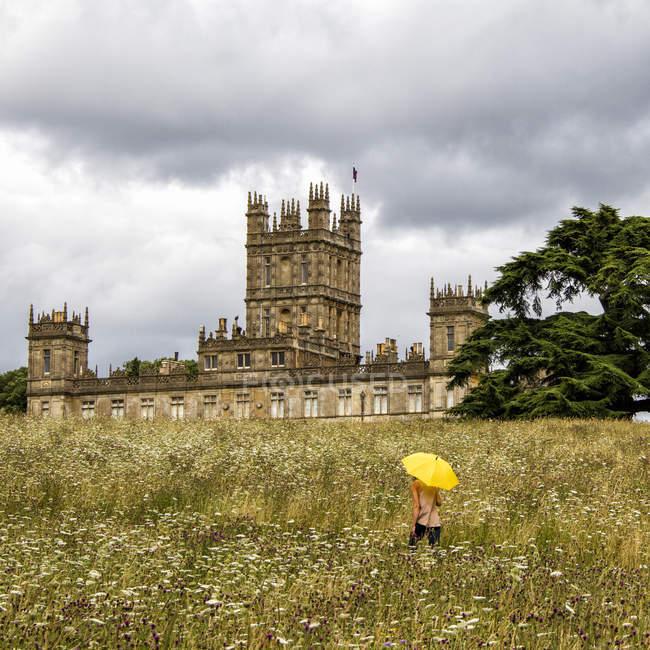 Femme avec parapluie jaune sur prairie, Highclere Castle, Hampshire, Royaume-Uni — Photo de stock