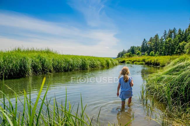 Rückansicht eines einsamen kleinen Mädchens, das im Fluss geht — Stockfoto