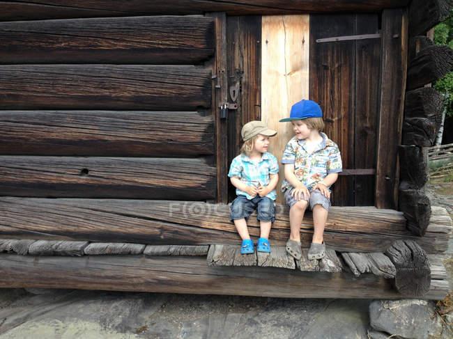 Два кавказских мальчиков с шапки, сидя на деревянное здание лестницы — стоковое фото