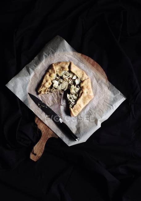 Fennel and mozzarella galette on parchment on wooden board — Stockfoto