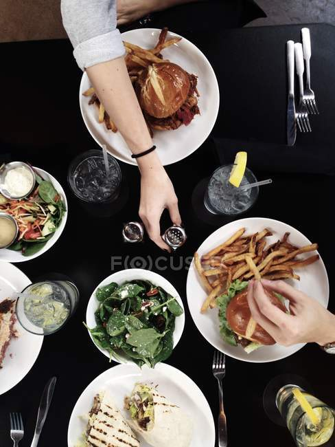 Top view of People enjoying burgers and wraps with salad — Stock Photo