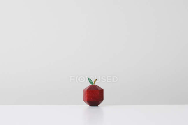 Red apple crafted into geometric shape imitating paper origami — Stockfoto