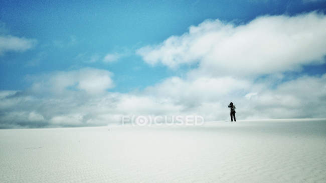 Silhouette of man standing in desert against blue sly with white clouds — Stock Photo