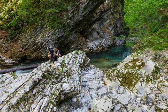 Man taking photo with camera on rock in nature, Vintgar Gorge, Slovenia — Stock Photo