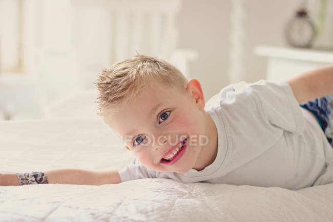 Portrait of happy blond boy lying on bed — Stock Photo