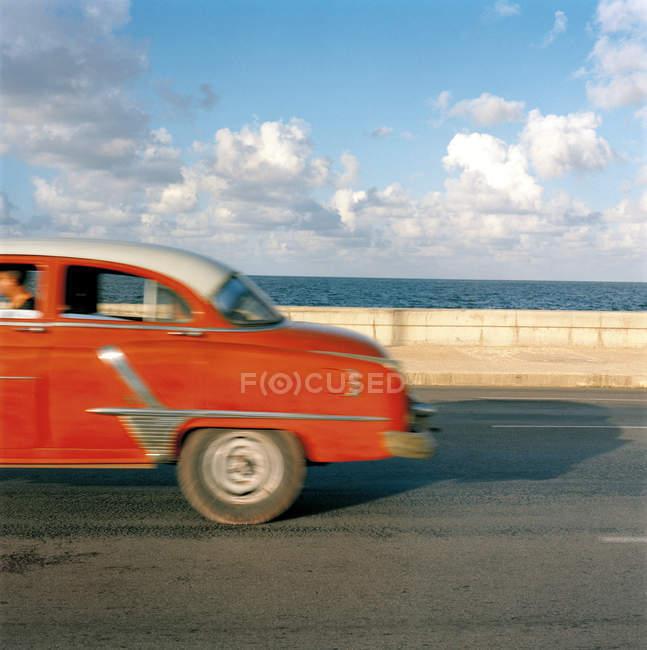Vista lateral del coche de época a lo largo de la orilla del mar, Cuba, Ciudad de La Habana, la Habana - foto de stock