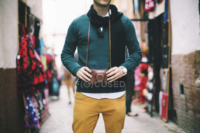 Close-up of Young man holding a vintage retro camera at market — Stock Photo