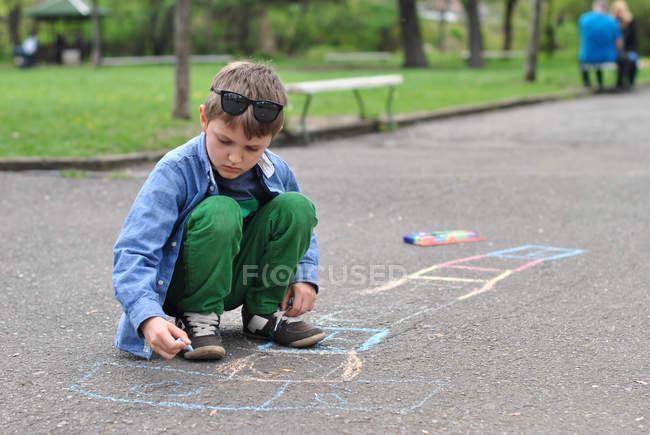 Niño dibujando azadón en el camino con tiza - foto de stock