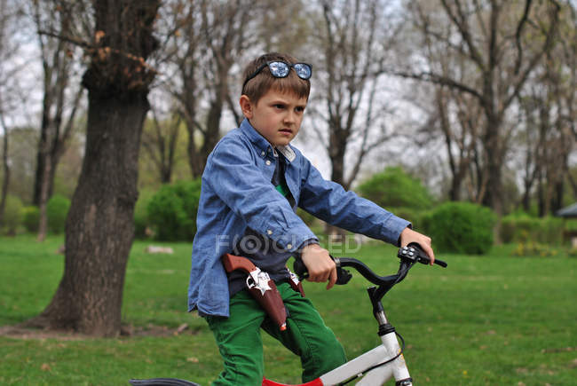 Boy pretending to be a policeman on bike in park — Stock Photo