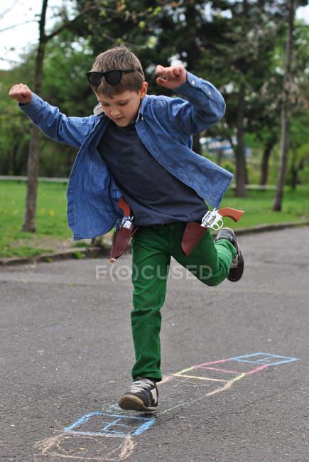 Chico jugando hopscotch en una pierna en la calle - foto de stock