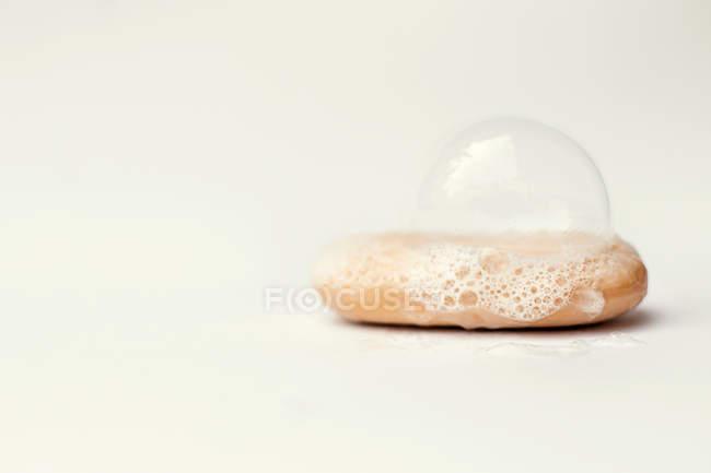 Bolhas na barra de sabão contra fundo branco — Fotografia de Stock