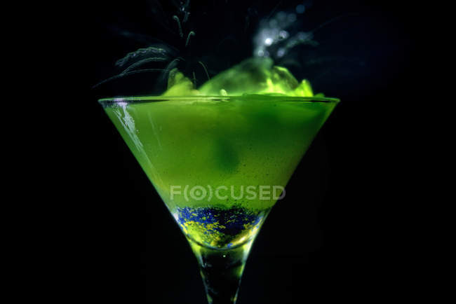 Green drink in a cocktail glass, black background — Stock Photo