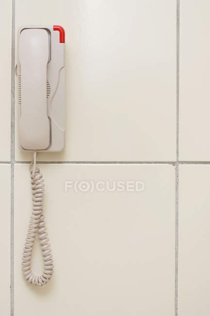 Closeup view of white phone hanging on wall — Stock Photo