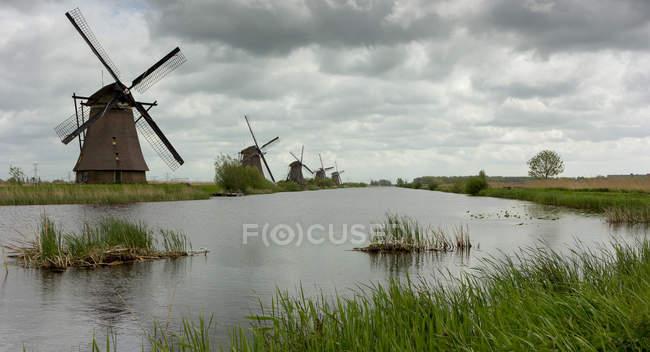 Vista panorámica de molinos de viento a lo largo del río, Kinderdijk, Países Bajos - foto de stock