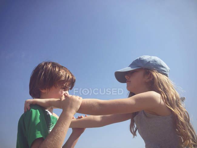 Seitenansicht von Bruder und Schwester unter blauem Himmel, Hände über den Schultern — Stockfoto