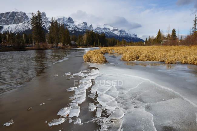 Zugefrorenen Fluss mit Blick auf Berge, Canmore, Alberta, Kanada — Stockfoto