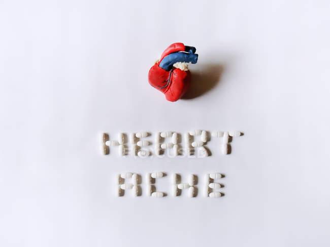 Coração conceitual e dor de cabeça feita de massa de jogo e pílulas — Fotografia de Stock