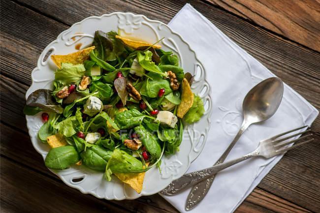 Ensalada verde con chips de tortilla sobre fondo de madera - foto de stock