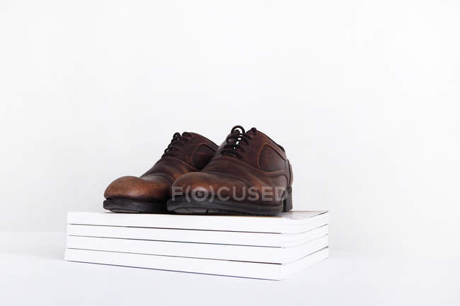 Pair of shoes on a pile of magazines, white background — Stockfoto