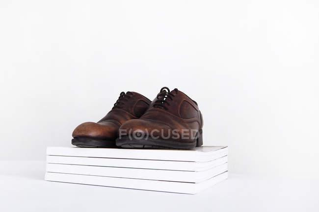 Paar Schuhe auf einen Haufen von Zeitschriften, weißer Hintergrund — Stockfoto