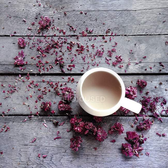 Mug of tea surrounded by dried flower blossoms — Stockfoto