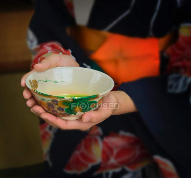Cropped image of girl holding cup of green tea — Stock Photo