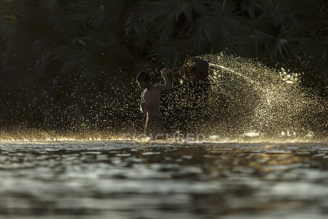 Conceptual image of two asian people in golden water splashes — Stock Photo