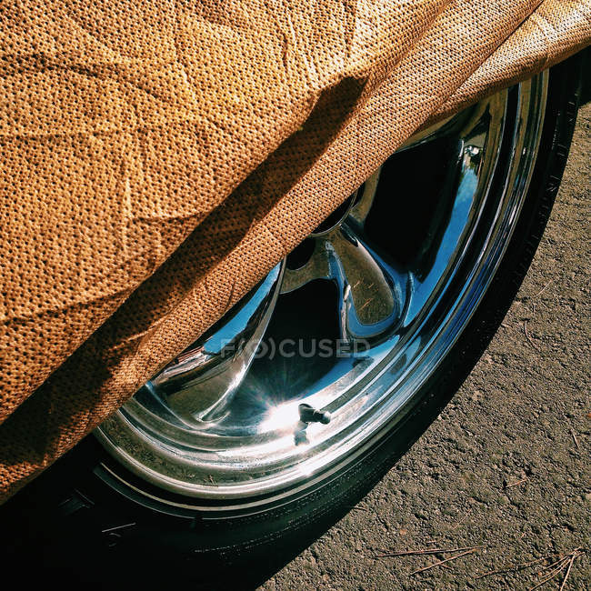 Close-up high angle view of Rim and car cover on asphalt road — Stock Photo
