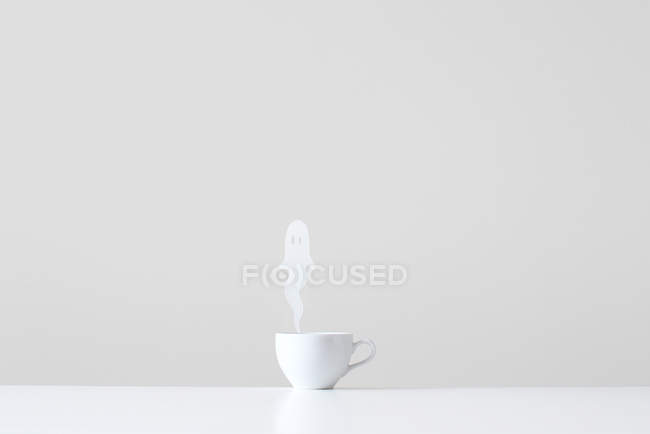 Conceptual cup with ghost steam against grey wall — Stockfoto