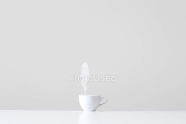 Konzeptionelle Tasse mit Ghost Dampf gegen graue Wand — Stockfoto