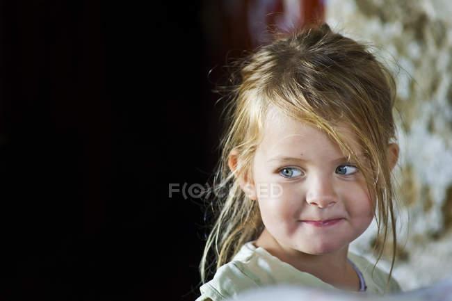 Retrato de cerca de una linda niña sonriendo y mirando hacia otro lado - foto de stock