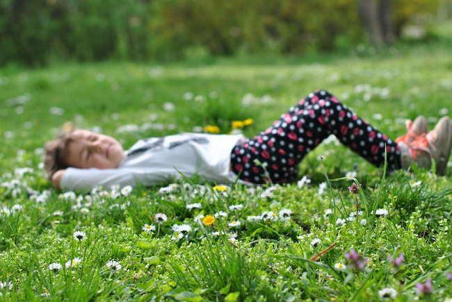 Menina deitada na grama com flor na primavera — Fotografia de Stock