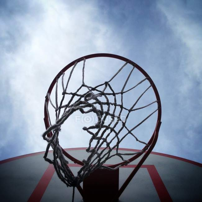 Low angle view of basketball hoop under cloudy sky — Stockfoto
