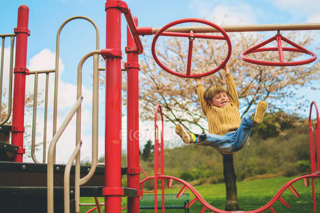 Cute little boy hanging from playground climbing frame and laughing — Stock Photo
