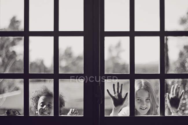Портрет двух милых игривых маленьких девочек, смотрящих в окно — стоковое фото
