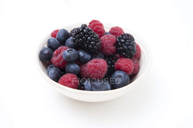 Fresh summer berries in bowl on white background — Stock Photo