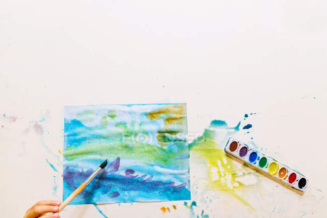 Overhead view of a boy painting with watercolors — Stock Photo
