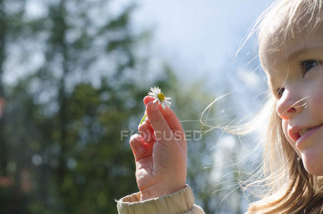 Portrait of a girl holding daisy flower — Stock Photo