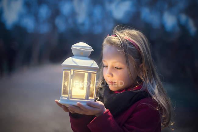 Chica pensativa sosteniendo una linterna en la noche - foto de stock
