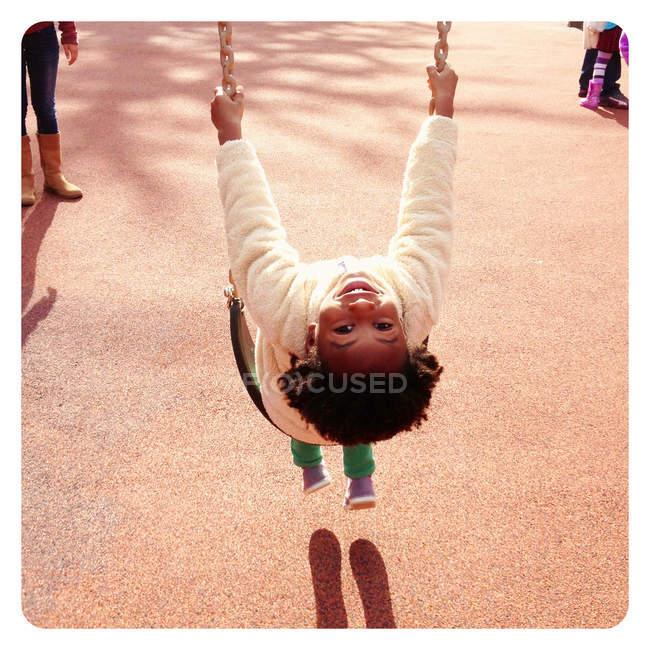 Retrato de una chica sonriente sentada en un columpio en el patio de recreo - foto de stock