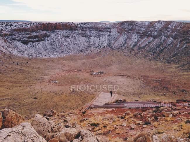 Живописный вид человека, идущего в метеоритный кратер — стоковое фото