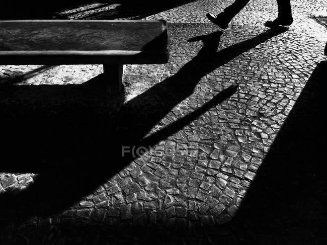 Immagine ritagliata di uomo che cammina sulla strada e getta ombra — Foto stock