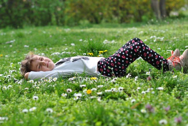 Menina deitada na grama com flores silvestres na primavera — Fotografia de Stock
