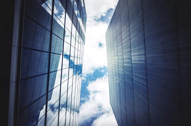 Vista inferiore di edifici per uffici con cielo e nuvole — Foto stock