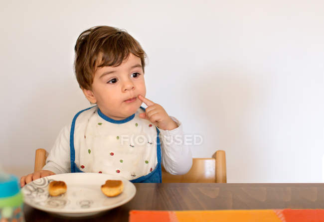 Thoughtful little Boy sitting at table eating — Stock Photo