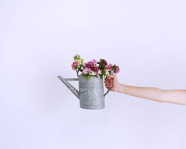 Mão humana segurando a garrafa de água com flores contra fundo roxo — Fotografia de Stock