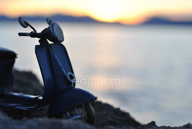 Closeup silhouette of a scooter parked by sea — Stockfoto