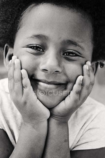 Ritratto ravvicinato di bambina carina con le mani sulle guance — Foto stock