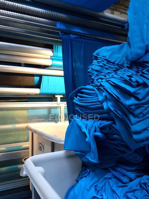 Closeup vista da fábrica de tecido com roupas azuis — Fotografia de Stock