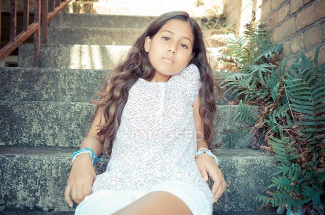 Retrato de la chica sentada en las escaleras al aire libre y mirando a la cámara - foto de stock